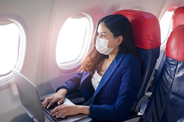 Una joven empresaria con máscara facial está usando una computadora portátil a bordo, nuevo viaje normal después del concepto de pandemia covid-19