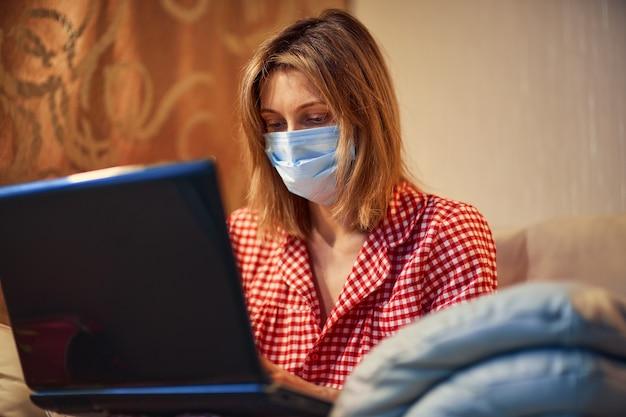 Joven empresaria en una máscara protectora médica trabaja desde casa