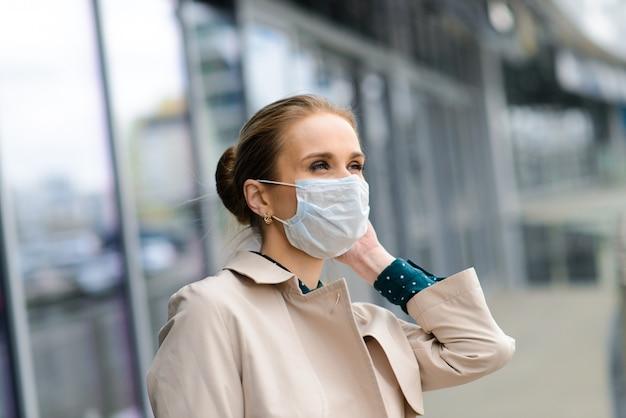 Una joven empresaria con una máscara de salud y hablando por teléfono en la ciudad