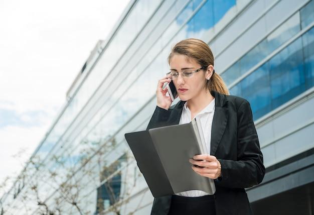 Joven empresaria mientras habla por teléfono celular mirando la carpeta