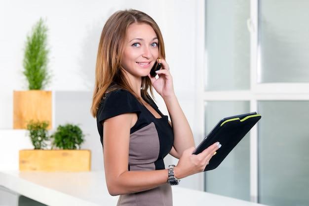 Joven empresaria en la moderna oficina brillante hablando por teléfono móvil y sosteniendo la tableta con una lista de tareas