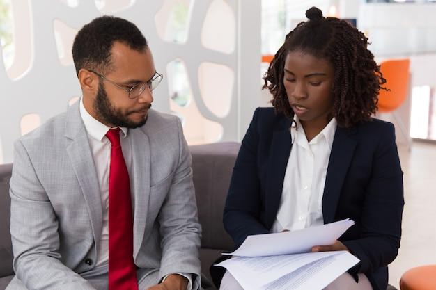 Joven empresaria mostrando contrato a colega masculino