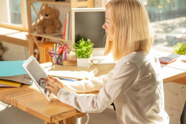 Una joven empresaria moviéndose en la oficina, consiguiendo un nuevo lugar de trabajo. joven oficinista caucásica equipa nuevo gabinete después de la promoción. usando tableta. negocio, estilo de vida, concepto de nueva vida.