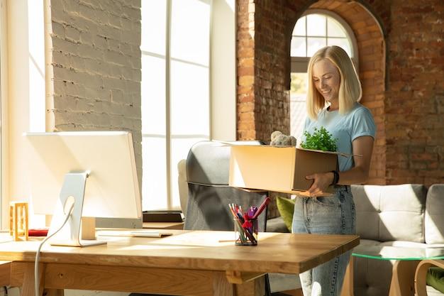 Una joven empresaria moviéndose en la oficina, consiguiendo un nuevo lugar de trabajo. joven oficinista caucásica equipa nuevo gabinete después de la promoción. se ve feliz. negocio, estilo de vida, concepto de nueva vida.
