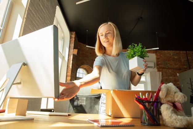 Una joven empresaria moviéndose en la oficina, consiguiendo un nuevo lugar de trabajo. joven oficinista caucásica equipa un nuevo gabinete después de la promoción
