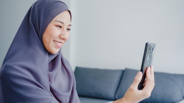 Joven empresaria musulmana de asia que usa un teléfono inteligente, habla con un amigo por videochat y hace una lluvia de ideas en línea mientras trabaja de forma remota desde casa en la sala de estar.