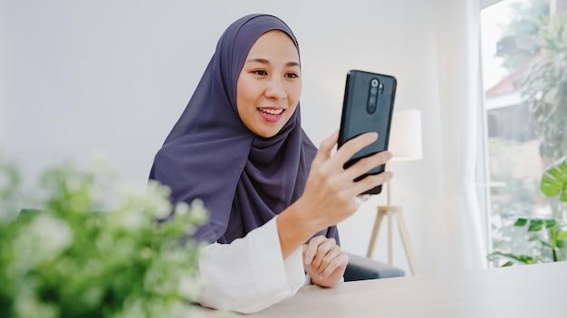 Joven empresaria musulmana que usa un teléfono inteligente, habla con un amigo por videochat, intercambia ideas en línea mientras trabaja de forma remota desde casa en la sala de estar.