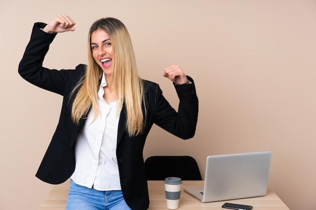 Joven empresaria en una oficina celebrando una victoria