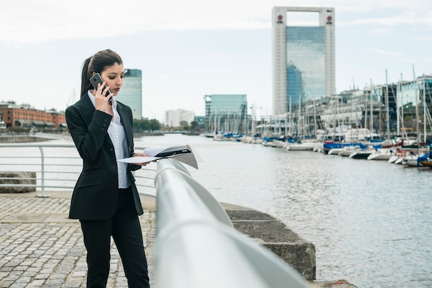 Joven empresaria de pie cerca del puerto
