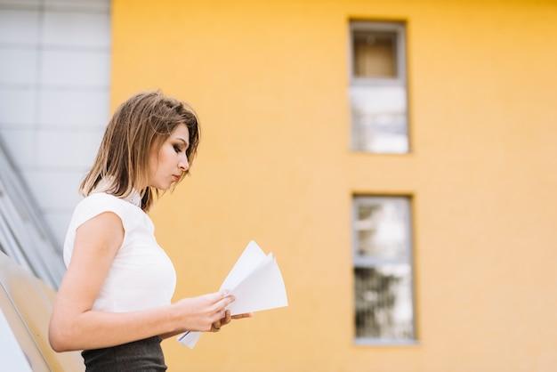 Joven empresaria de pie fuera de la oficina leyendo documentos