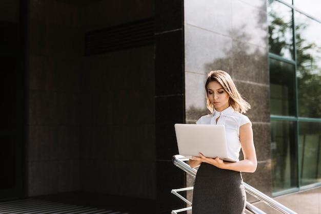 Joven empresaria de pie fuera de la oficina usando laptop