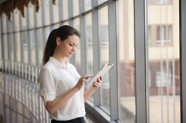 Joven empresaria de pie junto a la ventana con tableta