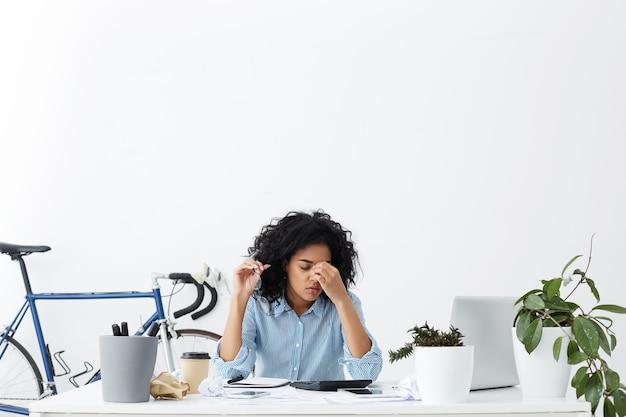 Joven empresaria de piel oscura estresada y frustrada que se siente cansada y con sueño