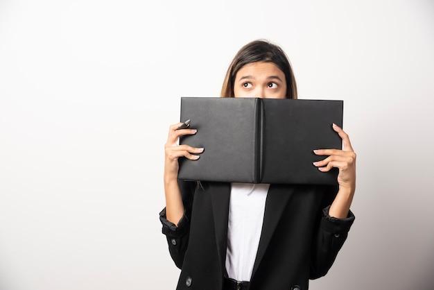 Joven empresaria que cubre su rostro con un portapapeles abierto. Foto gratis