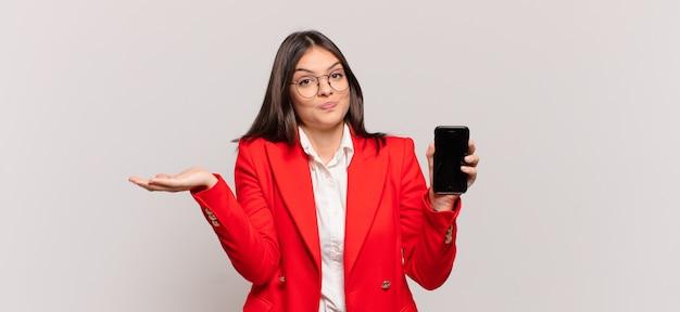 Joven empresaria que se siente desconcertada y confundida, dudando, ponderando o eligiendo diferentes opciones con expresión divertida
