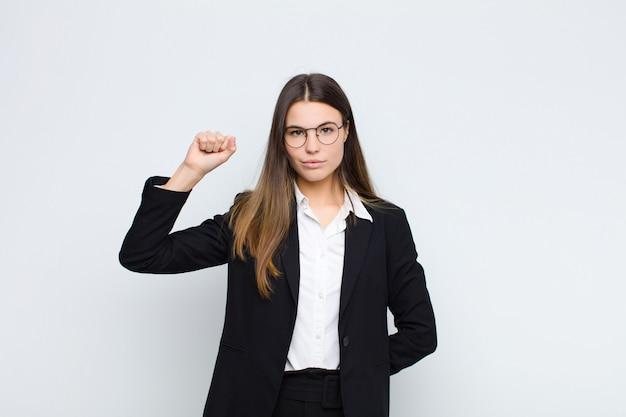 Joven empresaria que se siente seria, fuerte y rebelde, levantando el puño, protestando o luchando por la revolución sobre la pared blanca