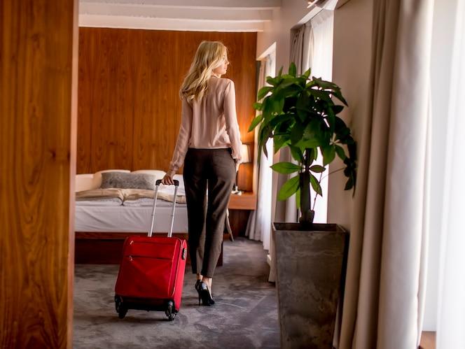Joven empresaria rubia llega a una habitación de hotel con maleta roja