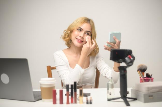 Una joven empresaria rubia que trabaja con una computadora portátil presenta productos cosméticos durante la transmisión en vivo en línea sobre un estudio de fondo blanco, vendiendo en línea y concepto de blogger de belleza