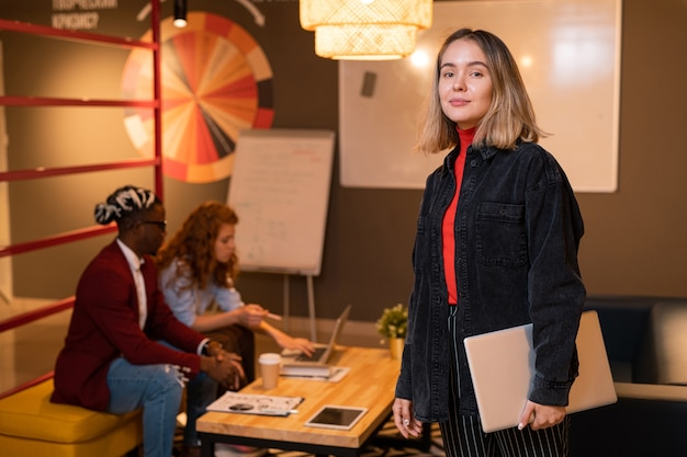 Joven empresaria rubia segura con portátil doblado