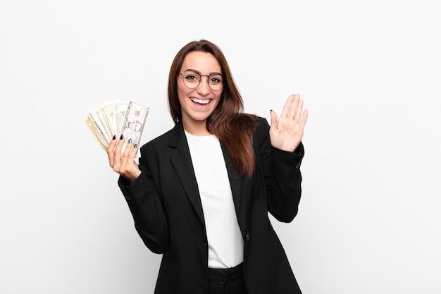 Joven empresaria sonriendo alegre y alegremente, saludando con la mano, dándote la bienvenida y saludándote, o diciéndote adiós con billetes de dólar