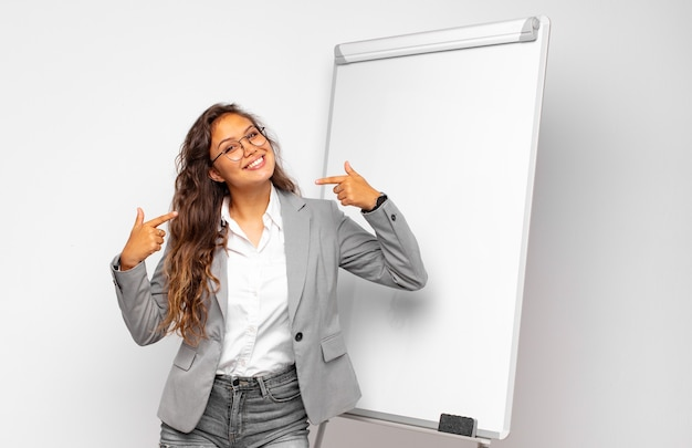 Joven empresaria sonriendo con confianza apuntando a su propia sonrisa amplia, actitud positiva, relajada y satisfecha