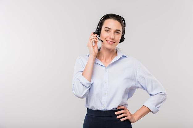 Joven empresaria sonriente en auriculares consultando a clientes mientras está de pie frente a usted de forma aislada