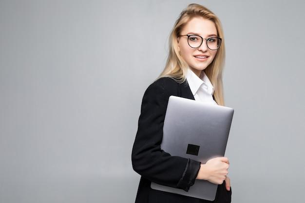 Joven empresaria sonriente feliz sosteniendo portátil aislado