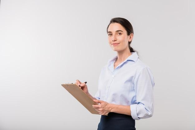 Joven empresaria sonriente en ropa formal haciendo notas mientras planifica el trabajo delante de la cámara