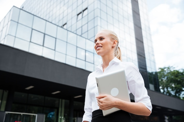 Joven empresaria sonriente sosteniendo tableta digital mientras mira lejos contra el edificio de oficinas