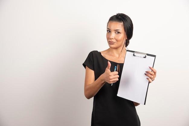 Joven empresaria sosteniendo documentos y mostrando el pulgar hacia arriba.