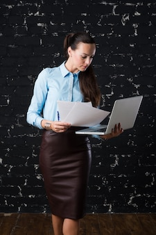 Joven empresaria sosteniendo una laptop