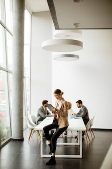 Joven empresaria con tableta digital frente a su equipo en una oficina moderna