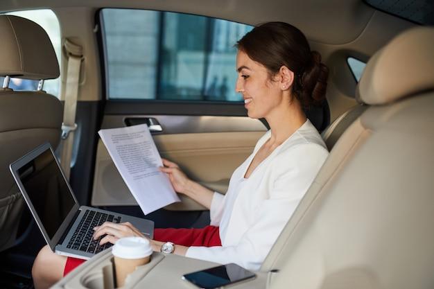 Joven empresaria trabajando en coche