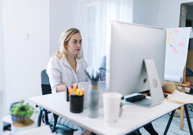 Joven empresaria trabajando en la computadora en la oficina