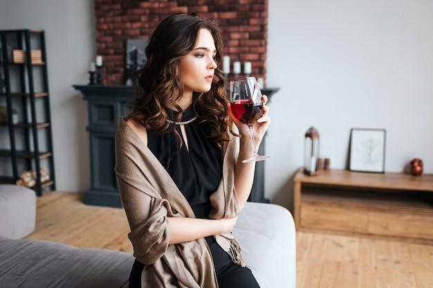 Joven empresaria trabajar en casa. reflexivo modelo tranquilo sostener copa de vino tinto y mirar hacia adelante. usa un vestido oscuro y un suéter marrón. solo en la habitación.