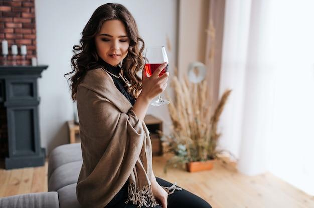 Joven empresaria trabajar en casa. sostenga una copa de vino tinto en la mano. hermosa modelo en vestido de noche de pie en la ventana. solo en la habitación.