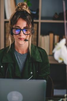 Joven empresaria usando anteojos y auriculares mientras usa la computadora portátil en el lugar de trabajo, hermosa mujer usando la computadora portátil. mujer vistiendo auriculares con micrófono, mirando la pantalla del portátil