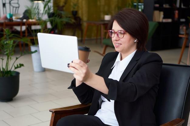 Joven empresaria con videollamada con tableta durante cofe break