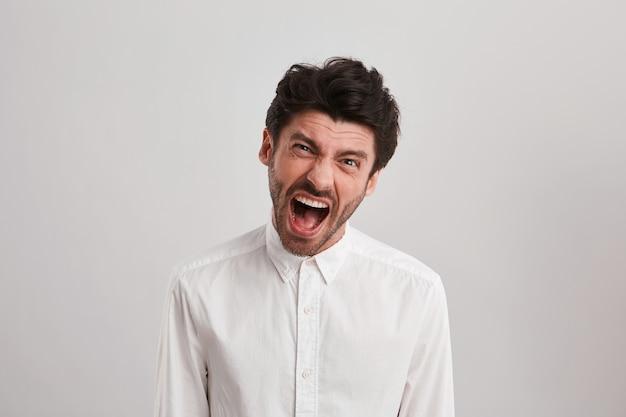 El joven empresario sin afeitar grita y se siente enojado y enojado, porque el proyecto no está terminado.