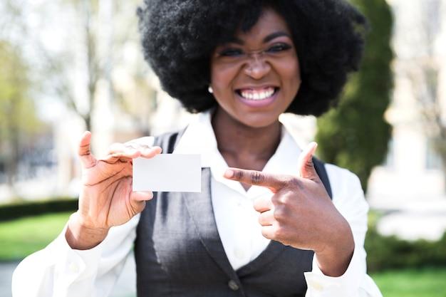 Un joven empresario africano apuntando su dedo a la tarjeta de visita