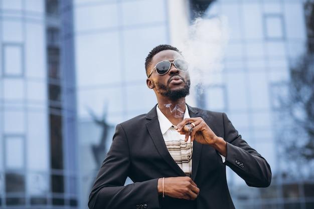 Joven empresario africano en elegante traje fumar cigarrillo