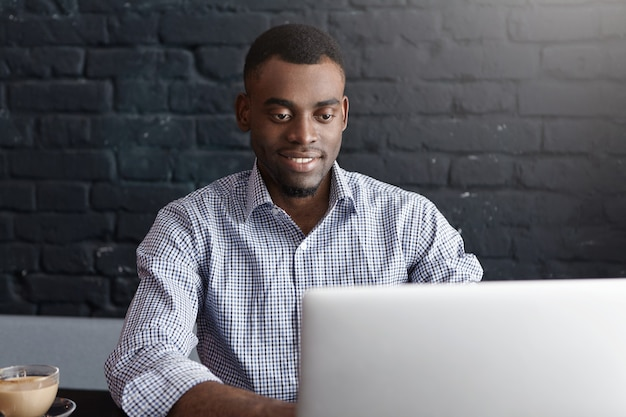 Joven empresario africano de éxito sentado en la mesa de café, trabajando en equipo portátil