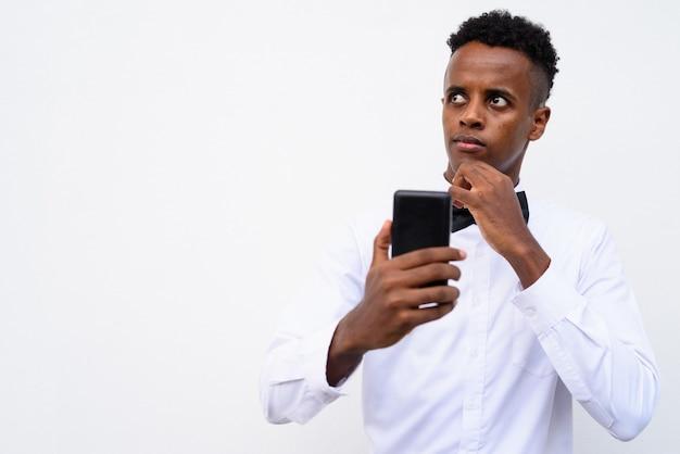 Joven empresario africano guapo mediante teléfono móvil contra el fondo blanco.