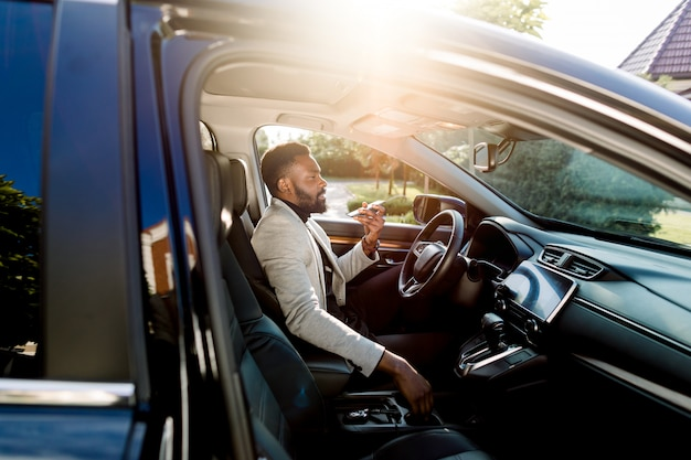 Joven empresario africano guapo usando el teléfono móvil, hablando por el altavoz, mientras está sentado dentro de un automóvil de lujo