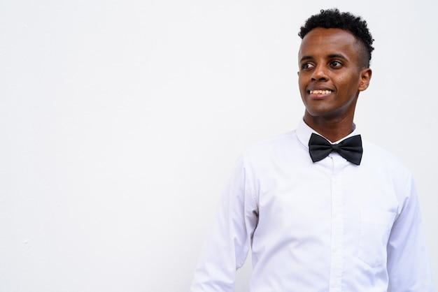 Joven empresario africano guapo vistiendo pajarita contra el fondo blanco.