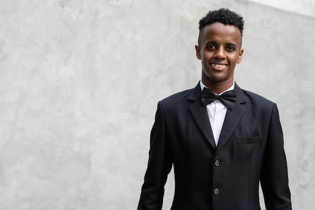 Joven empresario africano guapo vistiendo traje contra hormigón