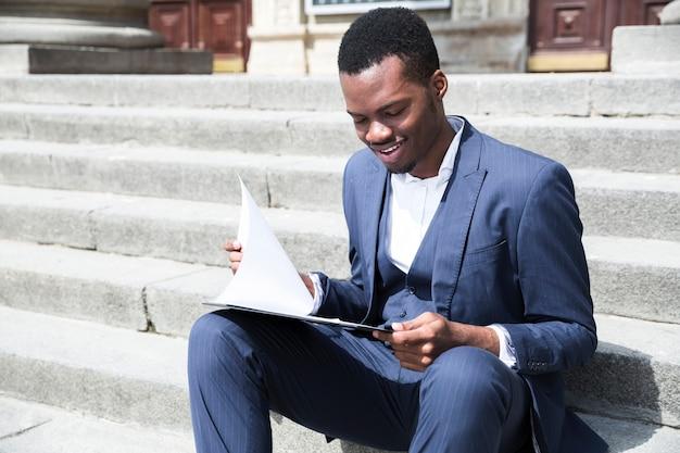 Un joven empresario africano hablando por teléfono móvil sentado en la escalera con la computadora portátil