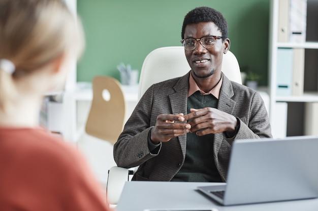 Joven empresario africano sonriendo y hablando con la mujer sentada en la mesa durante la reunión