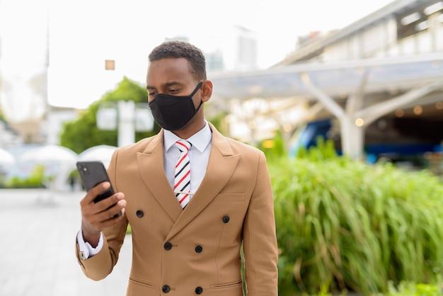 Joven empresario africano usando teléfono con máscara para protegerse del brote de coronavirus en las calles de la ciudad