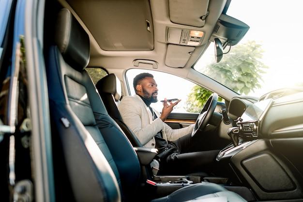 Joven empresario afroamericano exitoso hablando por altavoz a través del micrófono con el cliente, sentado en el coche caro. negociaciones y reuniones de negocios.